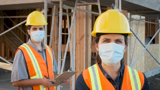 construction workers wearing a protective face mask working at a construction site - construction site stock videos & royalty-free footage