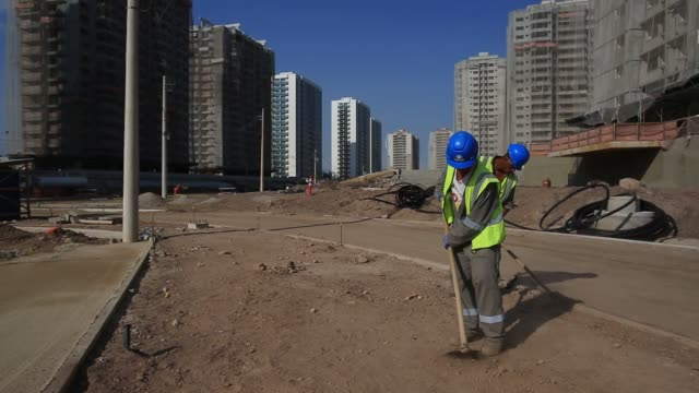 vídeos de stock, filmes e b-roll de construction workers work on building the ilha pura condominium complex in rio de janeiro brazil construction workers rake dirt and gravel with the... - condição
