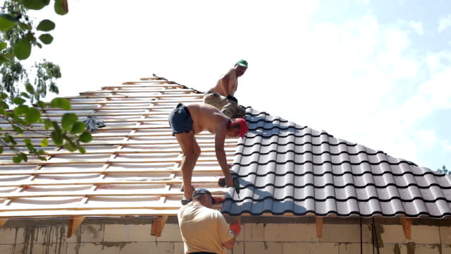 Construction workers work on the roof.