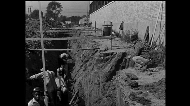 construction workers working in the ditch with wooden poles next to a wall - 1940 1949 stock videos & royalty-free footage