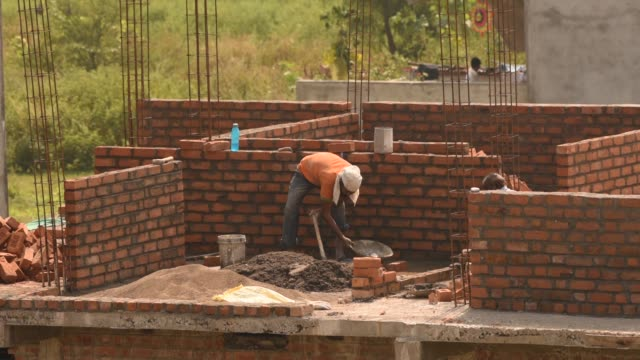 construction workers working on a building development site. - brick stock videos & royalty-free footage