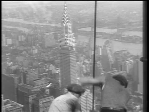 stockvideo's en b-roll-footage met b/w 1930 construction workers working on top of empire state building / chrysler building in background - chrysler