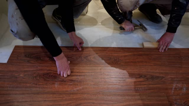 construction workers working with wood laminate flooring - flooring stock videos & royalty-free footage