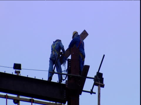 constructions workers in harnesses balance on girders as they work dubai - 桁橋点の映像素材/bロール