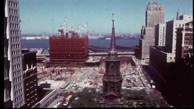 Constructions workers on site aerial view of WTC construction site north tower in early stages St Paul Chapel steeple in foreground
