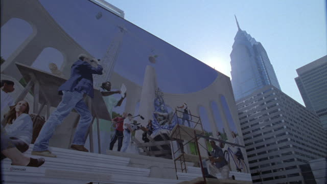 a construction-theme mural painted on a parking lot side of a downtown building in philadelphia. - mural stock videos & royalty-free footage
