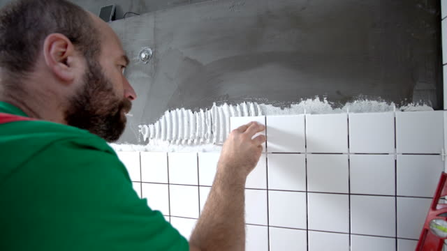 Constructor installing tiles on the bathroom wall