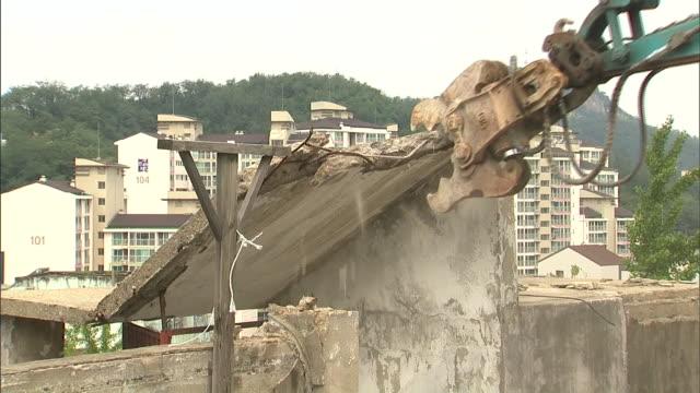 construncion vehicle breaking concrete of an old apartment - 全壊点の映像素材/bロール