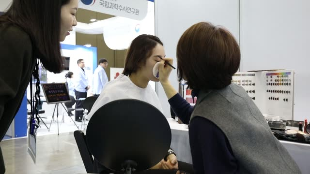a consultant speaks to a job seeker about makeup at a booth during a job fair in goyang south korea on saturday march 10 a consultant applies makeup... - goyang stock videos and b-roll footage