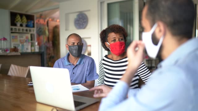 vídeos y material grabado en eventos de stock de consultor usando laptop y mascarilla facial. está dando consejos a una pareja en casa del cliente. - propiedad inmobiliaria