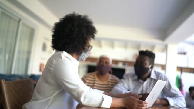 vídeos de stock, filmes e b-roll de consultor usando laptop e máscara facial. ela está dando conselhos para um casal na casa do cliente. - advogado