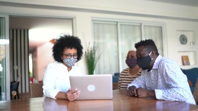 vidéos et rushes de consultant utilisant l'ordinateur portable et le masque de visage. elle donne des conseils à un couple chez le client - avocat juriste