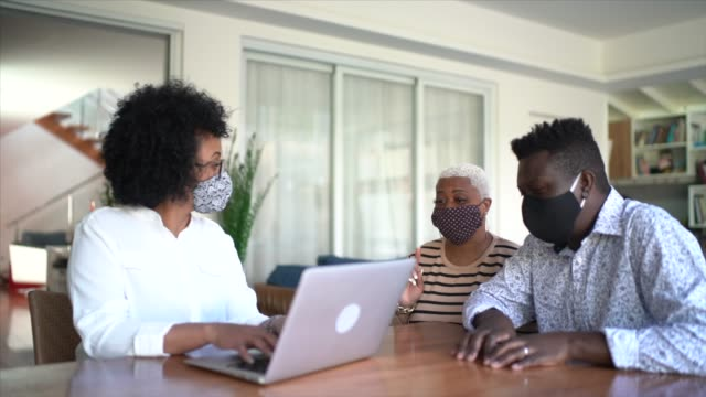 consultant using laptop and face mask. she's giving advice to a couple at customer's house - financial advisor stock videos & royalty-free footage