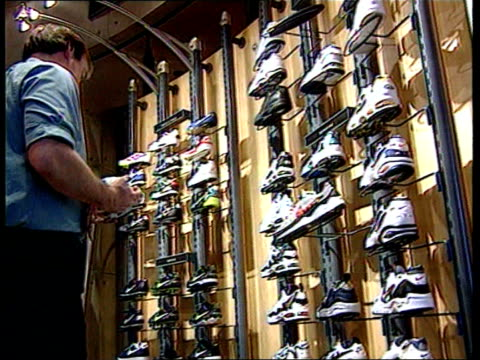 nike itn lib niketown sign on building int la customer looking at trainers displayed in shop sales assistant serving customer gvs people in trainer... - nike designer label stock videos and b-roll footage