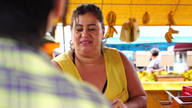 consumer buying banana at street market - market trader stock videos & royalty-free footage