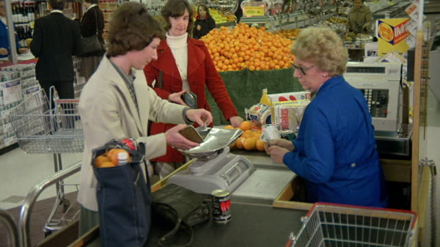 vídeos de stock e filmes b-roll de 1976 montage consumers pay for everyday purchases with cash / united kingdom - 1976