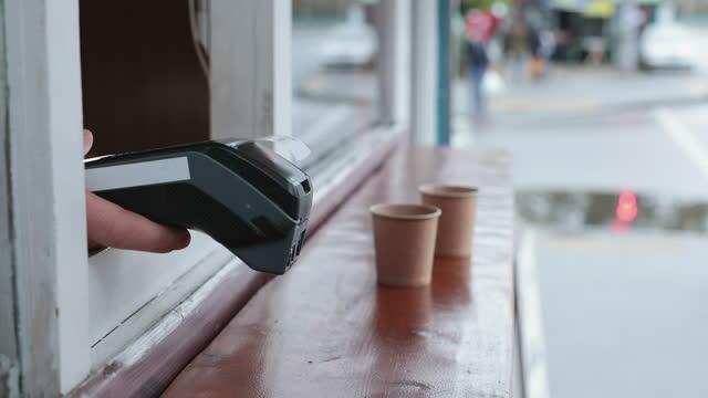 vídeos de stock, filmes e b-roll de pagamento sem contato usando um terminal de pagamento e um smartphone para comprar café em uma cafeteria de rua. - perto de