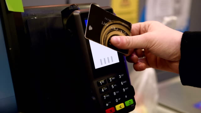 contactless payment with credit card at the supermarket checkout - 4k resolution - spending money stock videos & royalty-free footage