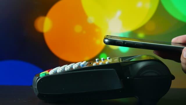 vídeos de stock, filmes e b-roll de pagamento sem contacto com o fundo de bokeh de luzes de discoteca - pagamento móvel