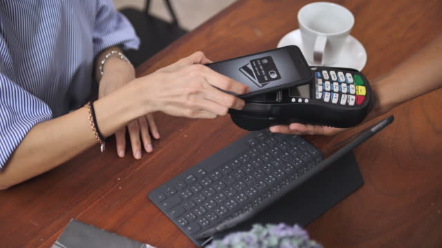 contactless payment with mobile phone in a cafe - paying card stock videos & royalty-free footage