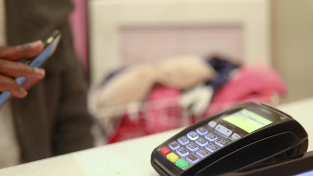 contactless payment with mobile phone in a shop - shopaholic stock videos & royalty-free footage
