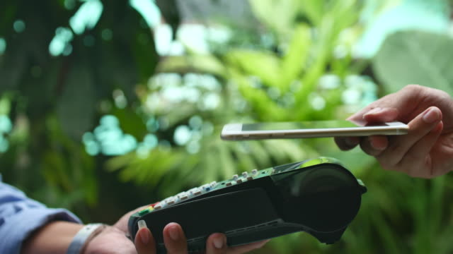 contactless payment with smart phone using nfc technology to pay - paying stock videos and b-roll footage