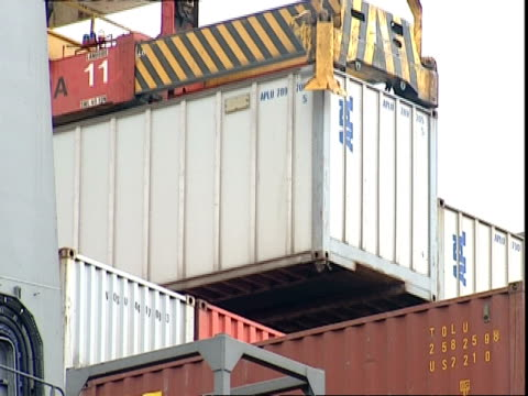 apl container being lifted from stack, container terminal, southampton, uk - schraubstock stock-videos und b-roll-filmmaterial