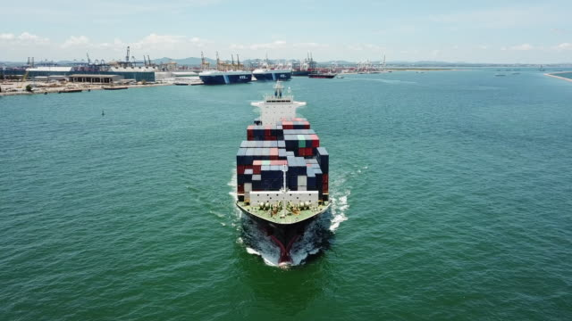 vídeos de stock e filmes b-roll de container cargo ship go out from harbor in ocean for export shipping - transportation