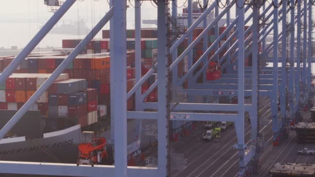 container cranes unloading cargo ship onto trucks - aerial - port of los angeles stock videos & royalty-free footage