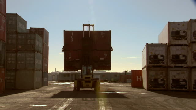 MS container handler driving away from camera carrying stack of cargo containers/ Sydney, Australia