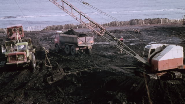 1978 montage container of coal being pulled, crane operator lifting and dumping container of coal onto truck, and truck driving / durham, england, united kingdom - durham england stock-videos und b-roll-filmmaterial