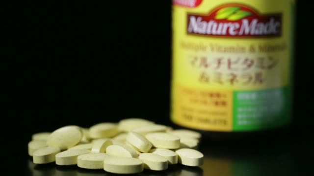 a container of nature made multiple vitamin minerals supplement imported by otsuka pharmaceutical co are arranged for a shot in tokyo japan on monday... - vitamin a nutrient stock videos & royalty-free footage