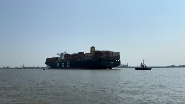 vídeos de stock e filmes b-roll de container ship and tug boat on the elbe river near hamburg - divisa