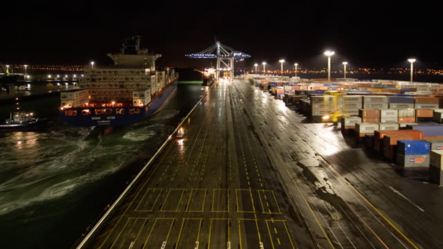 TL HA WS Container ship arriving at Ports of Auckland and being unloaded by cranes and straddle carriers from night to day/ Auckland, New Zealand