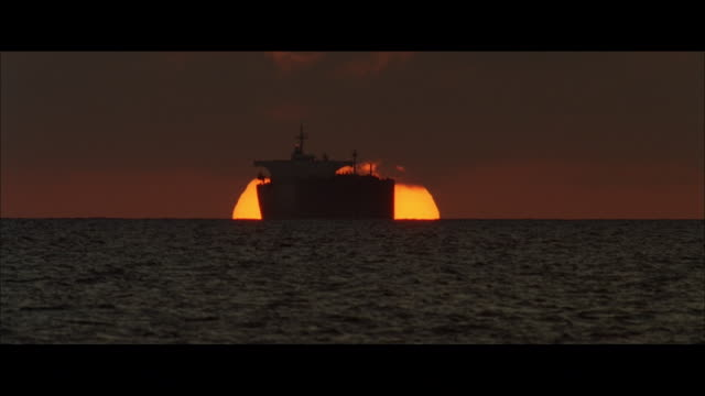 ws container ship at sunset, with the sun sliding into the sea - distant stock videos & royalty-free footage