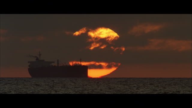 TU Container ship at sunset, with the sun sliding into the sea