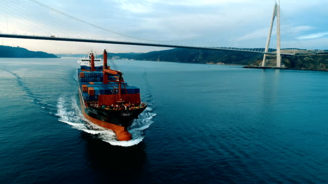 vídeos de stock e filmes b-roll de container ship crossing through the yavuz sultan selim bridge aerial drone footage - istanbul /4k - transporte de mercadoria