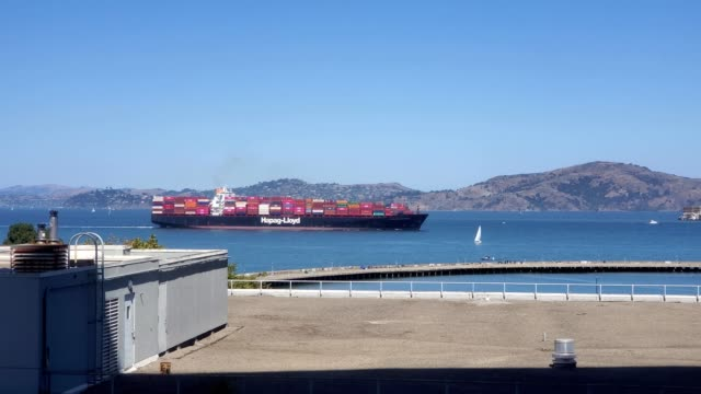 vídeos de stock, filmes e b-roll de a container ship from shipping company hapag lloyd is visible traveling through the golden gate into san francisco bay with buildings of downtown san... - baía de são francisco
