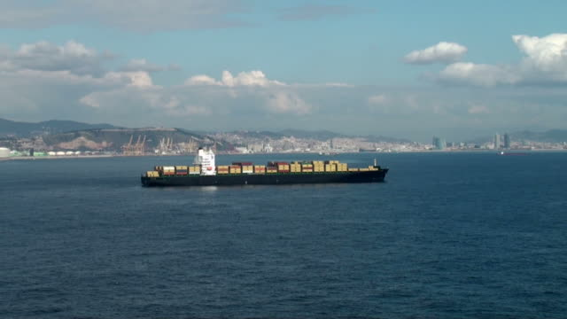 Container ship leaving Barcelona harbor in Spain; cityscape on background