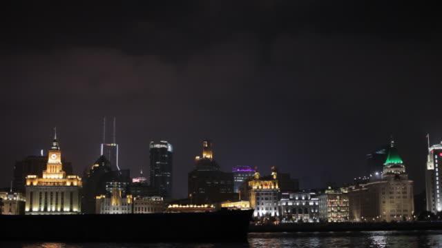 vídeos de stock e filmes b-roll de ws container ship moving past the bund skyline at night / shanghai, china - 1 minuto ou mais