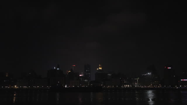 ws container ship moving past the bund skyline at night / shanghai, china - turning on or off stock videos and b-roll footage
