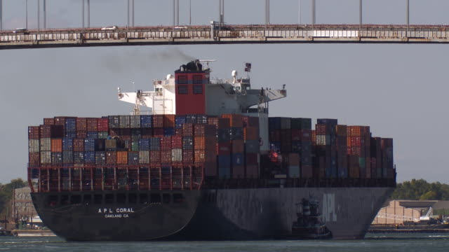 a container ship passes under the bayonne bridge with the aid of a tug boat. - lastkahn stock-videos und b-roll-filmmaterial