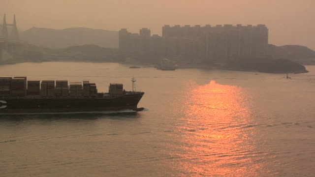 ms container ship passing ma wan channel near tsing ma bridge at sunset / hong kong, china - frachtschiff stock-videos und b-roll-filmmaterial