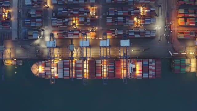 containerfartyg som arbetar på natten, business import exportlogistik och transport av internationella av containerfartyg i det öppna havet, flygfoto. - hamnanläggning bildbanksvideor och videomaterial från bakom kulisserna