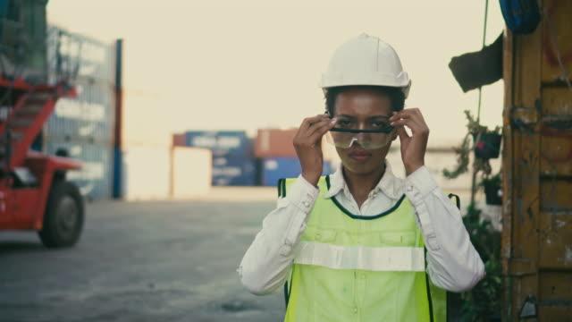 vidéos et rushes de les employés du terminal de conteneurs enfilent des lunettes de protection et croisent ses bras dans le port de navigation - pier