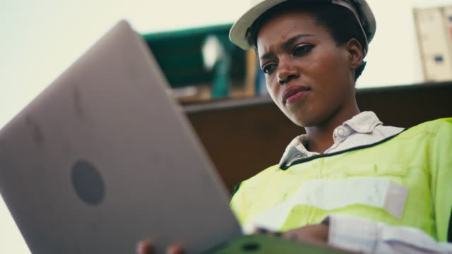 container terminal employees using laptop in front of cargo container stacks in shipping port - females stock videos & royalty-free footage