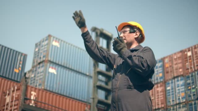 container terminal employees working in front of colorful cargo container stacks and container handler on background. - cargo container stock videos & royalty-free footage