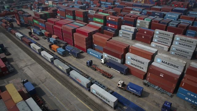 containers sit stacked as trucks move past in an aerial reverse and forward moving view taken above the uiwang inland container depot in uiwang south... - straddle carrier stock videos & royalty-free footage