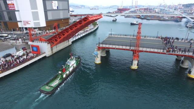 vídeos de stock, filmes e b-roll de containership passing below the yeongdo bridge - drawbridge