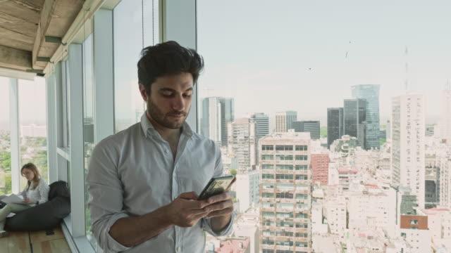 vídeos de stock, filmes e b-roll de empresário hispânico contemplativo olhando pela janela - ensolarado